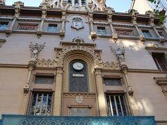 次は、カタルーニャ広場からランブラ通りを海に向かって進んでいきましょう。 ほどなく、「バルセロナ王立科学芸術アカデミー」が右手に現れます。 この建物は、かつてのイエズス会の学校の遺跡の上に、「ジョゼップ・ドメネク・イ・エスタパ」が建てた作品で、1894年に完成しました。 1764年に文学協会として設立されましたが、1887年に王立自然科学芸術アカデミーに改称したそうです。このアカデミアの図書室には、3世紀以上にわたる科学の発達に関する記録や著作、科学の歴史に関する資料など、10万冊を超える蔵書が収められているそうです。また1904年からは、ファブラ天文台との複合的な体制をとり天文学や地震、気象といった学問の分野における研究機関としての機能も果たしているそうです。正面の彫刻は、「マニェラ・ファクサ」による作品で、上部にあるドームと冠の形をしたドーム型の塔は、気象観測所と天文台です。 今は、1階に劇場もあります。
