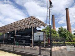 蒸気機関車の向こうに二本の煙突が見えています。