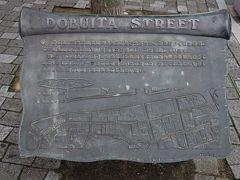 どぶ板通り。 横須賀市中心部にある全長300m程の通り・商店街で、スカジャンの発祥地として有名です。 第二次大戦前、この通りの中央にどぶ川が流れていましたが、人やクルマの通行の邪魔になるため海軍工廠より厚い鉄板を提供してもらい、どぶ川に蓋をした事から「どぶ板通り」と呼ばれるようになりました。その後ドブ川・鉄板ともに撤去されています。 店もすっかり様変わりし、正直つまんないんですよね