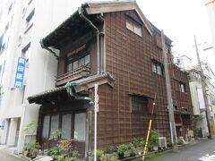 """神田駅西口から5分ほど、多町通り沿いに建つ一般住宅・松本家住宅主屋。 住宅の周囲はコンクリート製のビルばかりが建ち並んでいますが、この住宅だけは木造のためとても印象に残りました。雨樋には屋号の?長""""の文字が書かれていて、由緒ある建物であることがわかります。昭和6年に建てられた震災復興期の町家で、青果物問屋を営んでいたとのことです。現在もお住まいの方がいるため建物内を見学することはできませんが、屋根が現在少なりつつある瓦だったり、2階の窓ガラスに木製の障子の桟が映っていたりと趣が感じられました。"""