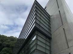 安藤忠雄建築と一発で分かるようなコンクリ感。  2つの三角形を重ね合わせたような建物。 ガラス部分は天気が良ければ山の緑や雲が写り綺麗なんだろうな、と想像 生憎の天気が悔やまれます・・・