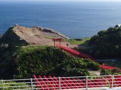 """正面の鳥居の前はやや広い広場になっていて、その先の断崖は人類黎明期の玄武岩で出来ており、""""龍宮""""という別称を有しています。その断崖の東側(右側)の一角に、「龍宮の潮吹」があります。 なお断崖絶壁岬の先端(写真左上)には2つのお地蔵さんがあり、海の安全を祈願してくださっていました(私の予想)。  お地蔵さんのすぐ先の断崖からは荒々しい日本海を180度見渡せますが、足元はゴツゴツとした岩でかなり危険です。"""