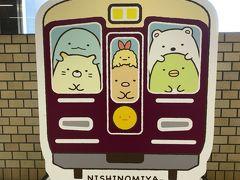 """カフェでの休憩だけじゃなくて、本日3カ所目のスタンプポイントも立ち寄るのを忘れないようにしないとね!  この駅のフォトスポットのパネルは、阪急電車にすみっコぐらしのキャラがギュウギュウに乗ってる感じでした。 電車の上にちょこんと座った、""""くり駅長""""がカワイイ!"""