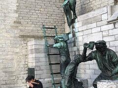 グルン広場の片隅にあるのは大聖堂の工事に従事している石工の姿だろうか。 その前でマンドリンを弾きつつ歌う青年の路上ライブ。