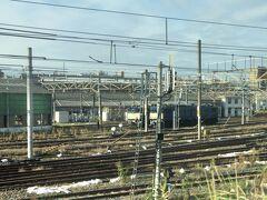 車窓に見えるは尾久客車操車場  青いレトロな機関車が2両並んでいます。