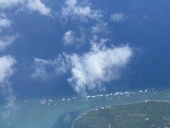 飛行機の窓から見えた島の写真。何島かははっきり分らないけど港らしきものが見えます。島の周りはサンゴ礁みたい。人が住んでいるのが分かります。後から調べてみると形状から見て鳩間島のようです。