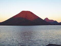 目を転ずると、夕日に照らされた榛名山が見えました。富士山に似た形の良い山で、別名「榛名富士」とも呼ばれます。 麓から榛名山頂まで行けるロープウエーがありますが、夕方なので営業は終了(のぼり最終時間:16:30、往復料金:大人850円)しています。頂上からの眺めが良いとのことですので、次回、もっと早い時間に来て、登ってみたいと思います。  夕暮れで、林の中を走る道路も暗くなってきました。宿のある伊香保温泉は榛名山を下った東北、約10kmです。宿に向かいます。