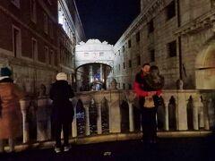 ライトアップで浮き立つポンテ・デイ・ソスピーリ Ponte dei Sospiri ため息の橋。  ドゥカーレ宮殿と牢獄を結ぶ、白の大理石で造られた溜息の橋、嘆きの橋。  ため息橋という名前は、運河に架かる渡り廊下で、尋問室(これは拷問室という意味)や牢獄に行く囚人が、橋を渡る際に『これが最後』とため息をつくというところから、バイロン男爵が1810年代に執筆した『チャイルド・ハロルドの巡礼』の中でBridge of Sighsと呼んだのが初めなんだそうです。  橋が建設された頃には厳しい取調べや刑執行は行われていなく、独房も短期のものだったそうなので、そうと知ると心があまり痛まず見れますが、当時は酷く恐ろしい扱いを受けると街で噂されていたそうです。  今では恋人たちのロマンティックなデートスポットになった橋。