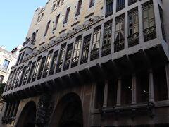 バルセロナ一の繁華街「ランブラス通り」を、地下鉄「リセウ」駅から100メートルほど海へ向かって下ったあたり右側にある「ノウ・デ・ラ・ランブラ通り」という細い道に入って、50メートルほど進んだところに「グエル邸」は建っています。 邸宅全体を正面から写真の画角に収めることはできないほど細い道に立っているので、ちょっとびっくりです。ここはラバル地区といって、今もガイドブックには、夜道の一人歩き厳禁とされている治安の悪い地区であり、グエル邸が建てられた頃も貧しい人々が住む地域だったそうです。 グエル氏は、この場所に建てるからこそ、皆をあっと言わせるような邸宅を建てたいとの願いがあり、ガウディはそのグエル氏の願いを受けて、縦18メートル横22メートルという限られたスペースに最高の邸宅を建てようと考えました。グエル氏はブルジョアのグエル氏がここに住むことで、ラバル地区の悪い雰囲気を変えたいとも思っていたそうです。  ガウディは、伝統的な高貴な材料(石材、木材、鍛造鉄、セラミックス、ガラスなど)を使用し、その才能を惜しみなくつぎ込んで、「モデルニスモ建築の宝石」とも称されるこの邸宅を作りあげました。もちろんパトロン本人の邸宅ですから、予算は潤沢だったわけです。  ちなみに、このグエル邸は、ガウディが最初から完成まで携わることができた唯一の邸宅です。貴重ですね!