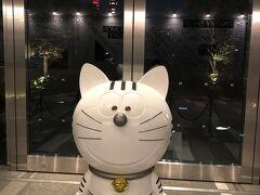 『虎ノ門ヒルズ』のキャラクターとして誕生した「トラのもん」の オブジェの写真。  「トラのもん」は22世紀のトーキョーからタイムマシンに乗ってきた ネコ型ビジネスロボットです。  赤くライトアップした東京タワーをバックにパチリ ( -_[◎]o