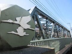 木場橋の先にある鶴歩橋。 平久川にかかる40mほどの深緑色をした、鉄製の頑丈な橋です。かつてあった鶴歩町という名から橋の名がつけられたようです。親柱には二羽の鶴が舞っている姿が描かれています。