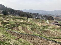 駅から、10分ほど歩いて行くと、棚田のエリアに。 季節によっていろんな色彩になるのが想像できます。 まだ春先ですので、田んぼの中は土が見えています。