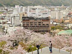 天守閣跡から。張り出したようなテラスと桜。遠景はホテルだ