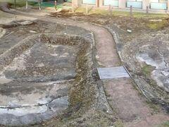 この木簡が発見されたのは、万葉文化館中庭の溜め池あと。これは発掘現場を忠実に再現したレプリカで、オリジナルはこの地下4mに埋め戻されました。 飛鳥池工房遺跡とよばれ、古代の工房がありました。この工房では、7世紀後半から8世紀初め、金属製品、宝石、漆工芸品などを制作したようです。当時の超ハイテク、美術工芸品工房でありました。
