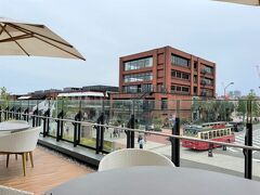 横浜・みなとみらい『インターコンチネンタル横浜Pier 8』の レストラン&バー【Larboard(ラーボード)】のテラス席からの 眺めの写真。  お昼時なので、複合施設『マリン アンド ウォーク ヨコハマ』も 人がちらほら。周遊バス「あかいくつ」もパチリ。