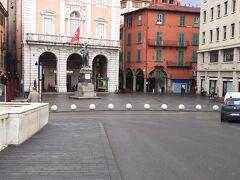 ガリバルディ広場には向かって右手にピンクと白の建物、右手にテラコッタ色の建物があり、広場には像がたっています。