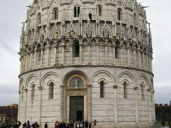 ピサの斜塔の近くには他にもいくつか大理石でできた建物があります。  こちらはサンジョバンニ洗礼堂です。  高さはあまりない建物でころんとした形が特徴です。  外側にはたくさんの彫刻があります。  屋根にも特徴があります。瓦がついてるところとついていないところがあります。写真右手の一部はついています。  ついていないのは資金不足によるものです。海風の影響を受けやすいため西側のみ瓦をつけて東側はつけることができませんでした。  これが現在もそのままの状態でのこっているのが面白いです。