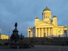 朝日に輝くヘルシンキ大聖堂。白亜の壁が美しい。 大階段のある元老院広場に面している。 大きな彫像はアレクサンドル2世の像。 フィンランド国会を再建したことを記念して建てられた、とウィキペディアにはある。 ホテルから歩いて5分ほど。
