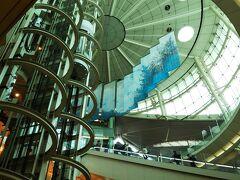 「第2ターミナル」といえば、この吹き抜けホール☆ 展示用のおベンツ(車)が置いてある辺りから撮るとこんな感じ。  天井から吊るされている、青い吊るしの作品は日本画家「千住 博」の作品。 「第2ターミナル」は青チーム系の「全日空」ターミナルなので、青系の色なのかもしれません。笑  そして、耳を澄ませば聞こえるかもしれない「千住 明」作曲、「千住真理子」のバイオリン演奏の曲、というわけで、ここは千住兄弟のホール☆笑  ついでに言えば、目が疲れたので千寿製薬の目薬でも上を向いて点したとしたら、あなたは既に「センジュ」に包まれているかもしれません。笑  そして、あの屋根のデザインはエンジンをイメージしているのか、 それとも飛行機のケツに付いている「後部圧力隔壁(機内の圧力と外の圧力を隔てている壁)」のイメージなのか、よくわからず。笑