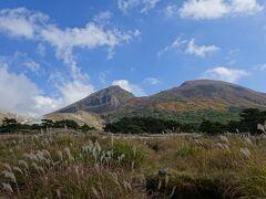 """鹿児島市街から約2時間、""""霧島山""""を構成する山の1つ【韓国岳(からくにだけ)】の麓へやってきました。ここはえびの高原の入口(少し宮崎県へお邪魔中)です。 紅葉とススキに彩られた山の風景がとても綺麗です。  """"霧島山""""は、20を超える火山が集まって構成されている""""連峰""""です。構成する山で代表的なものは、2018年に大噴火した新燃(しんもえ)岳や、高千穂峰、そして写真の韓国岳などがあります。周辺は、多数の火山湖があり、ハイキング・登山コースとして人気です。ここへ来る途中の登山者用の駐車場はほぼ満車でした。また機会があれば登ってみたいです。  高原を一周する予定でしたが、この時は2018年の新燃岳噴火で大型のレストハウスは軒並み休業、道路がほとんど通行止めでした。残念、リサーチ不足でした。"""