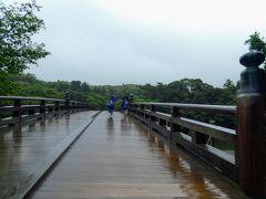内宮に到着。 宇治橋を渡ります。 遷宮の4年前に架け替えられるのだそうです。 外宮では左側通行でしたが内宮は右側通行。 しかーし、そんなことが言えないぐらいの強い風雨。 前に歩いているお2人のレインコートと傘の様子から風が強いのが伝わりますかね?
