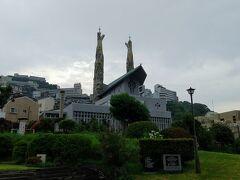 その奥は聖フィリッポ教会、 アントニオ・ガウディを日本に紹介した、今井兼次によるもの。 2本の塔は聖母マリアと聖霊にそれぞれ捧げられている。