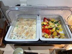 一晩明けて朝7時(つω-)ネムネム 今回は800円の朝食バイキングを付けたので、1階フロント横のお食事会場へ向かいます。 ちょうど熱々の料理が用意されたところだった。  メイン料理(?)はグラタンと夏野菜のグリル。ズッキーニとパプリカ美味しいー。 大好物のグラタンがあるのもポイント高い。