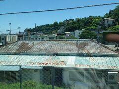 三島行きの電車から眺める景色。 「真鶴駅」に到達。 色あせた「二匹の鳥と虹の絵が描かれた屋根」の建物が面白い。