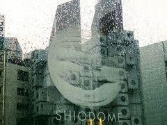 SIO-SITEの文字の向こうに中銀カプセルタワー ガラスは雨に濡れているけどね。