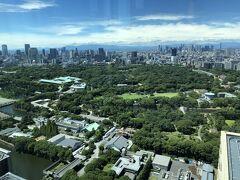 東京・大手町『フォーシーズンズホテル東京大手町』39F【PIGNETO】  イタリア料理【ピニェート】からの眺望(西側)の写真。  『皇居宮殿』と『宮内庁庁舎』の右側には、「皇居東御苑」が 広がります。 写真中央奥に『国立競技場』、写真右奥に新宿の高層ビル群が見えます。  写真右の石垣が見えているところは「江戸城本丸跡」になります。