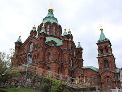 """このウスペンスキー大聖堂もヘルシンキ大聖堂と同じく、小高い丘の上に立地。  建てられたのは1862年から1868年にかけて、ロシア人建築家アレクセイ・ゴルノスターエフの設計によるもので、""""ウスペンスキー""""とは、カトリックの""""聖母被昇天""""に当たる""""生神女就寝""""(しょうしんじょしゅうしん)という意味。  したがって、このウスペンスキー大聖堂、日本語直訳では、""""生神女就寝大聖堂""""となります。"""