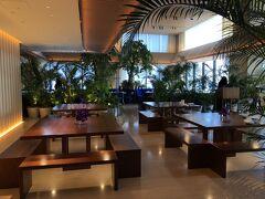 """東京・神谷町『The Tokyo EDITION, Toranomon』31F  『東京エディション虎ノ門』の31階のシーティングエリアの写真。  こちらのスペースもバー【Lobby Bar】のアフタヌーンティー時に 使用しています。  写真奥は、オールデイダイニング【The Blue Room】です。 宿泊した翌朝、ブレックファストをいただきました。  木材の自然素材がふんだんに使われた洗練された空間です。 ロビーラウンジの壁には、オーク材を使った""""大和張り"""" (板を一枚ずつずらして少し重ねて貼る方法)が採用され、 ロビーラウンジそのものが人々がさまざまな目的で集う 寺院の境内をイメージし、庇(ひさし)を巡らせた 二重構造になっています。"""